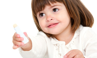 Portrait of little girl with lip balm.